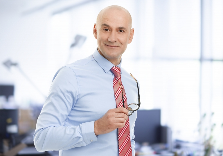 Portrait of senior businessman standing at office. Business people holding eyewear in his hand while smiling and looking at camera.